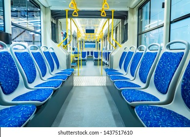 Empty city bus salon. Public land transport within the city. Seating for passengers. Handrails for holding. Contactless payment transport validators. Passenger urban transport.