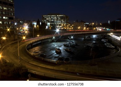 Empty city traffic ramp at night with parking lot