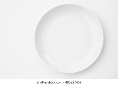 Empty classic white plate on white background. View from above.