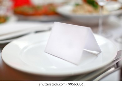 Empty classic white plate in a restaurant with a blank card and copyspace for example guest names.
