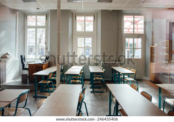 Empty classroom with large windows and old furniture