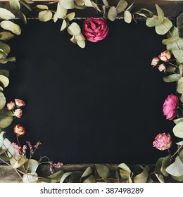 Empty clean black wreath and chalkboard with pink and red roses and green leaves around it. Overhead view. Flat lay, top view