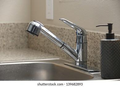 Empty clean kitchen sink and soap dispenser