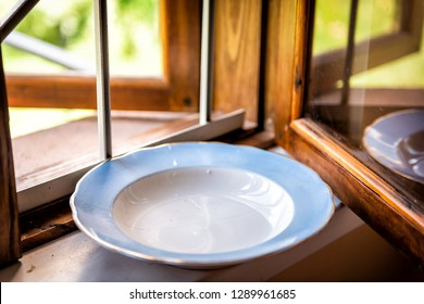 Empty clean washed plate on windowsill window sill by garden in rustic summer house in Ukraine called dacha