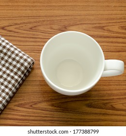 empty coffee cup on brown kitchen towel and wood table