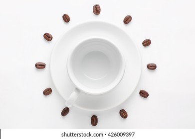 Empty coffee cup on saucer and coffee beans against white background forming clock dial viewed from above. Concept is time to drink morning coffee.