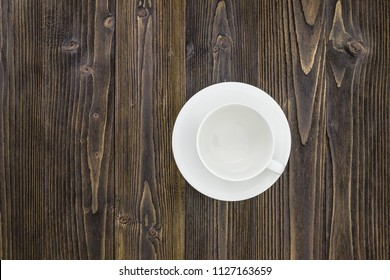 Empty coffee cup on wooden table background.