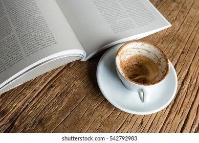 empty coffee cup with coffee stain next to an open book on wooden table