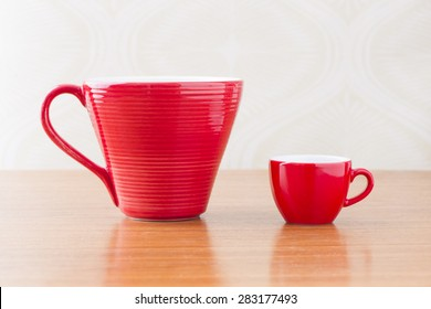 Empty coffee cups on wooden table in home interior.
