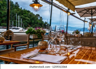 Empty coffee and restaurant terrace with tables and chairs in Portofino sunset.
