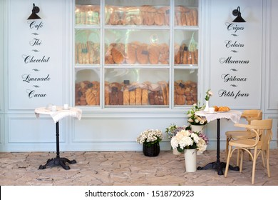 Empty coffee and restaurant terrace with tables and chairs in French style. Freshly baked pastries and bread in bakery showcase. Street cafe decoration, interior concept. outdoor cafe. Decor bakery.