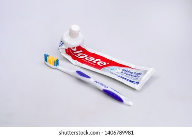 Empty Colgate Toothpaste and Colgate Toothbrush on a white isolated background.