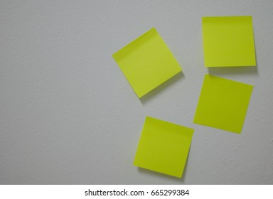 Empty color paper sheet on white wall with sticky glue for add text message and short note