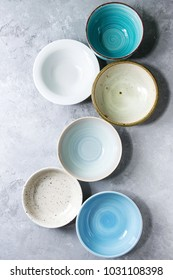 Empty colorful ceramic bowls collection. Various of dishware grey texture background. Top view