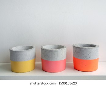 Empty colorful modern geometric concrete planters on white shelf isolated on white background. Beautiful painted concrete pots.