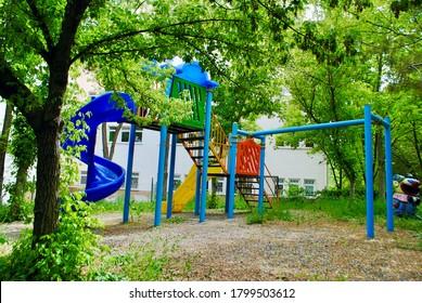 Empty colorful playground park with big trees and thick weeds due to coronavirus, Covid-19. Cayyolu Ankara Turkey