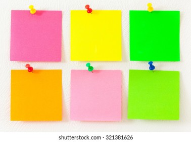 Empty colorful post its on the wall with push pins.