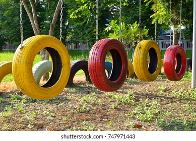 Empty colorful of recycled old tires swings in children playground