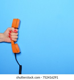 Empty comic book yellow cloud next to retro orange phone tube held by woman hand - Flat lay
