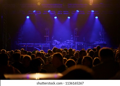 Empty concert stage with crowd in front blue stage lights