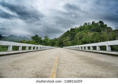Empty concrete bridge with natural view, tropical green mountain and cloudy sky in rainy season. Rural local road of Thailand. Death end, deadlock, stuck concept. Travel and road construction design.