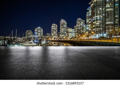 empty concrete square floor with harbor background at night