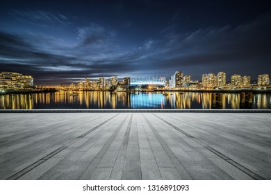 empty concrete square floor with skyline background at night, vancouver, canada.