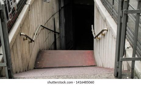 Empty concrete stairwell towards dark underground tunnel