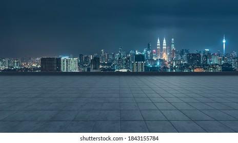 Empty concrete tiles floor with city skyline background. Night scene