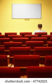 empty conference hall. rows of a chairs. focus on a first row. one man sitting in chair