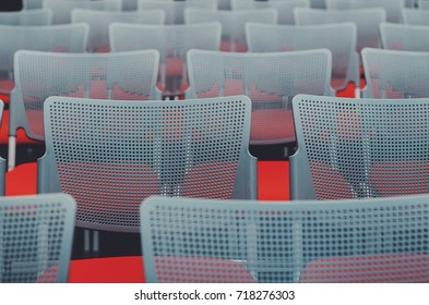 An empty conference and meeting room full of red chairs.