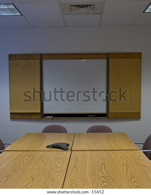 An empty conference room with whiteboard, and conference phone