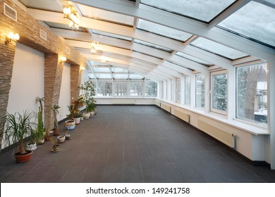 Empty conservatory with small number of plants and glass ceiling in cottage at winter.