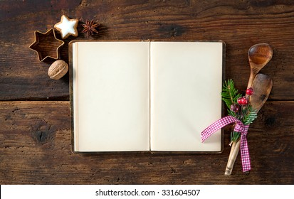 Empty cookbook for Christmas recipes on wooden table