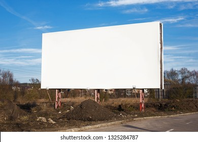 Empty copy space blank white bilboard with blue cloudy sky in the background.