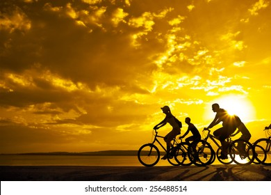 Empty Copy Space Sporty company friends on bicycles outdoors against sunset Silhouette five 5 cyclist going along shoreline coast Reflection sun on water Sport in Nature background Group of people