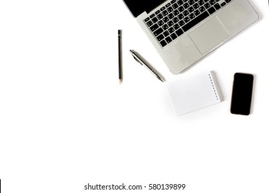 Empty copyspace in left corner and center. Minimalistic workplace with laptop keyboard, smartphone, notebook, pen and pencil on white background. Flat lay