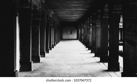 An empty corridor with pillars portrayed in black and white belonging to an old Indian Fort.