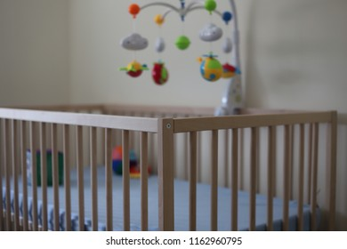 An empty cot with toys and cot mobile