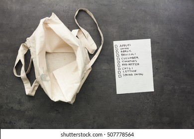 Empty cotton shopping bag with shopping list. Food shopping concept.