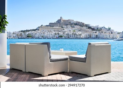 an empty couch at the Mediterranean Sea, with Sa Penya and Dalt Vila districts, the old town of Ibiza Town, in the background, in the Balearic Islands, Spain