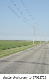 An empty country road disappears into the distance on a summer afternoon