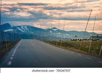 Empty country road in Norway, Europe, Scandinavia. Auto travel on sunset. Orange sky with clouds.