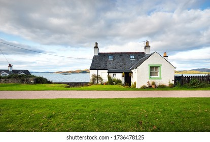 An empty country road and small traditional house on the rocky shore of Crinan canal. Hills and forest in the background. Dramatic cloudscape. Travel destinations theme. Scotland, UK