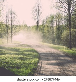 empty country road in spring forest with perspective and shadows - retro vintage grainy film look
