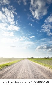 Empty country road through the fields against cloudy blue sky, Latvia. Dramatic cloudscape. Idyllic rural scene. Agricultural, fuel and food industry, alternative energy, environmental conservation