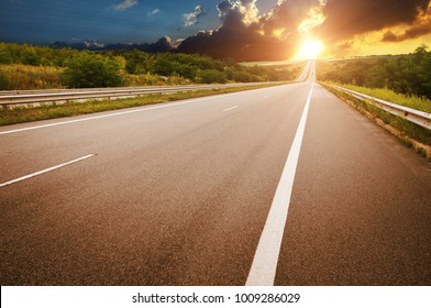 An empty countryside road against a night sky with a beautiful sunset
