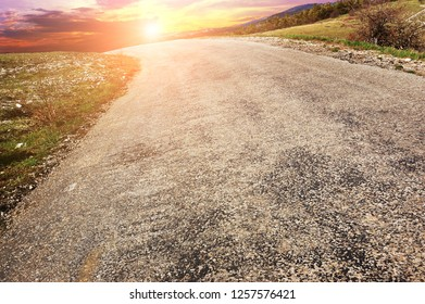 An empty countryside road with grass and forest against a night sky with a beautiful sunset