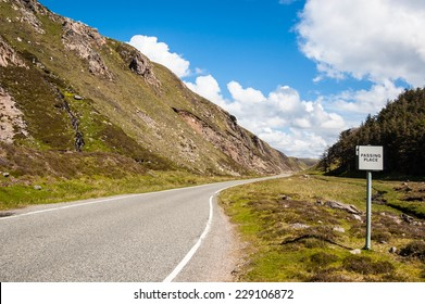 Empty countryside road in the Scottish highlands with a passing place sign on the side in a sunny day