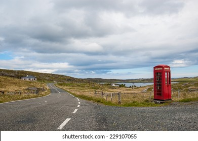 Empty countryside road in the Scottish highlands with a traditional British red telephone box  on the side